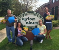 Picture of Custom Alarm Employees in front of their sign with donated items for United Way