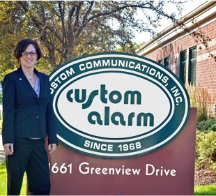 Melissa Brinkman standing by Custom Alarm sign in front of building