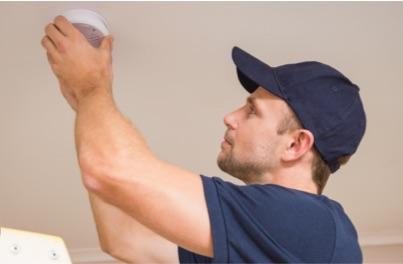 man installing smoke detector
