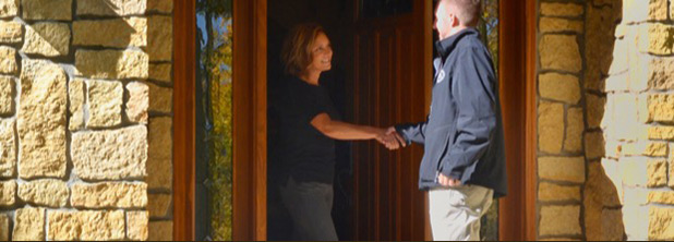 Image showing a Custom Alarm installer shaking hands with a woman on the front steps to her home