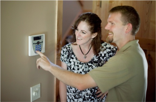 Husband and wife using keypad on alarm system
