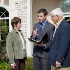 Realtor explaining something to clients in front of house